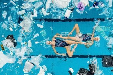 Synchro swimmers perform in a pool filled with plastic